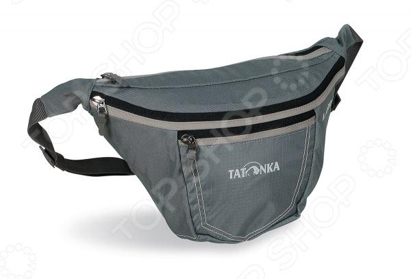 Сумка поясная Tatonka Ilium L это отличный способ носить с собой необходимые мелочи и при этом не занимать руки. Такую сумку по достоинству оценят любители путешествий и прогулок на велосипедах. У сумки регулируемый ремень, а также есть второй карман на молнии и переднее отделение с перегородкой.